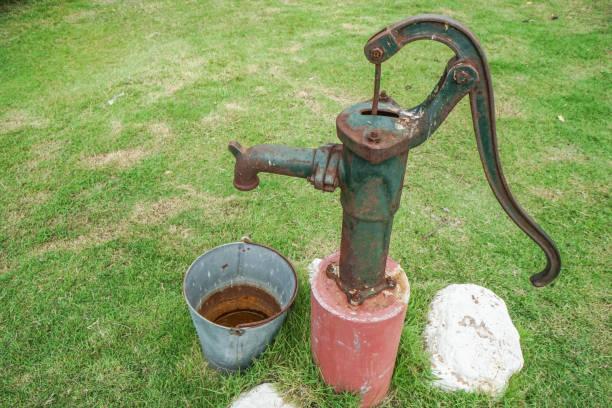old and rusty vintage water pump with stainless bucket - tap water zdjęcia i obrazy z banku zdjęć