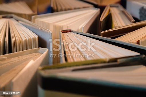 istock Old and used hardback books, text books seen from above on wooden floor. Books and reading are essential for self improvement, gaining knowledge and success in our careers, business and personal lives 1040308012