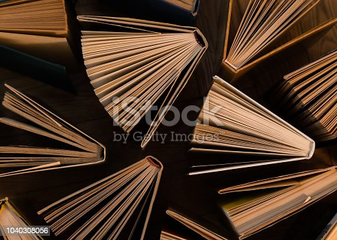 istock Old and used hardback books, text books seen from above on wooden floor. Books and reading are essential for self improvement, gaining knowledge and success in our careers, business and personal lives 1040308056
