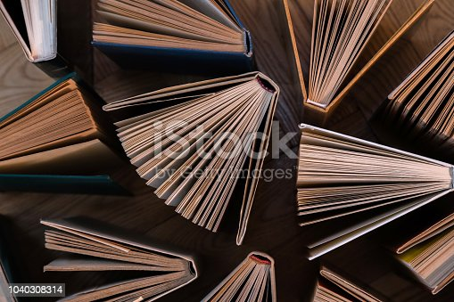 istock Old and used hardback books, text books seen from above on wooden floor. Books and reading are essential for self improvement, gaining knowledge and success in our careers, business and personal lives 1040308314