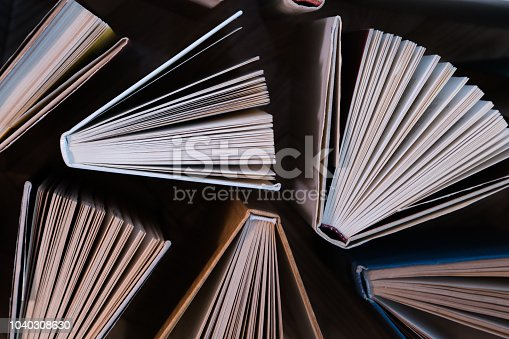 istock Old and used hardback books, text books seen from above on wooden floor. Books and reading are essential for self improvement, gaining knowledge and success in our careers, business and personal lives 1040308630