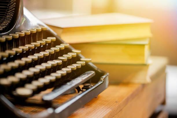 alt und vintage art schriftsteller maschine und haufen bücher auf holztisch - sehr selektiven fokus - stockwerke des waldes stock-fotos und bilder