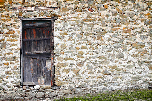 Old and weathered wooden door on very old stone wall taken in full frame on medieval house facade architecture