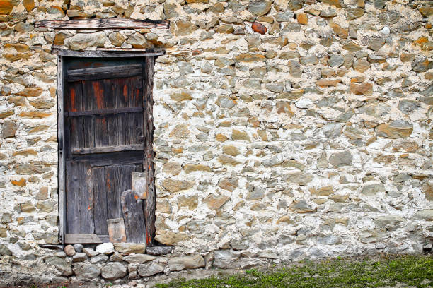 Old and weathered wooden door on very old stone wall taken in full frame on medieval house facade architecture stock photo