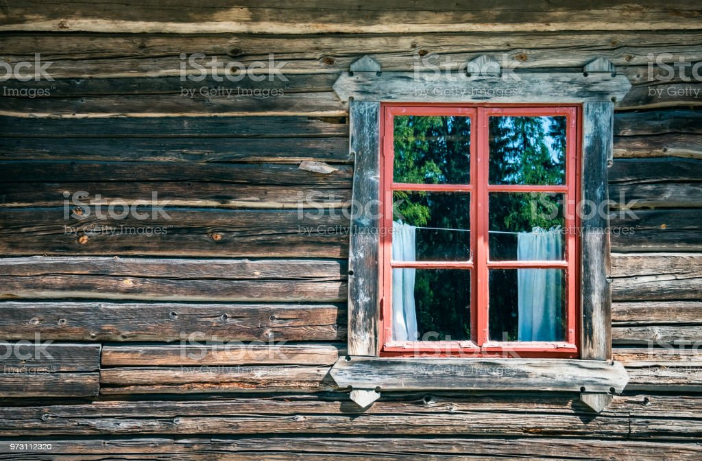 Old and worn timber wall with window at abandoned cottage. stock photo