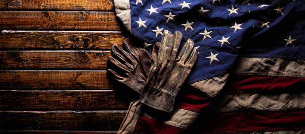 Old and worn work gloves on large American flag - Labor day background Old and worn work gloves on large American flag - Labor day background labor union stock pictures, royalty-free photos & images