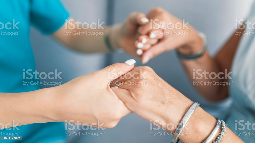 Old and young holding hands on light background stock photo