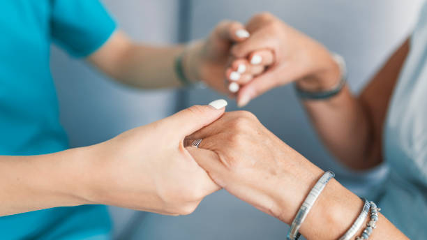 Old and young holding hands on light background Old and young holding hands on light background, closeup. Helping hands, care for the elderly concept. Care is at home of elderly. Woman with caregiver at home neurodegenerative disease stock pictures, royalty-free photos & images