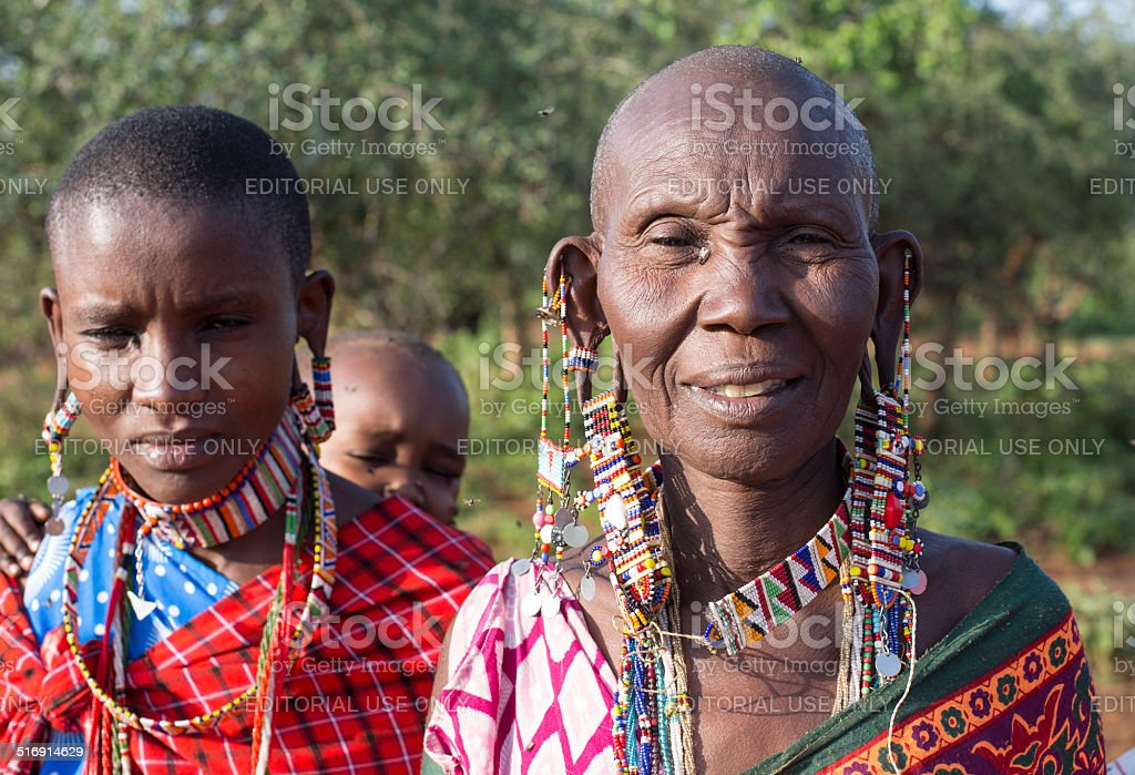 Old and young maasai women with baby and traditional jewellery stock photo