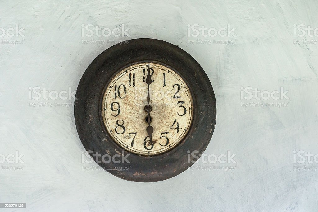 Old antique cracked clock hanging on white wall