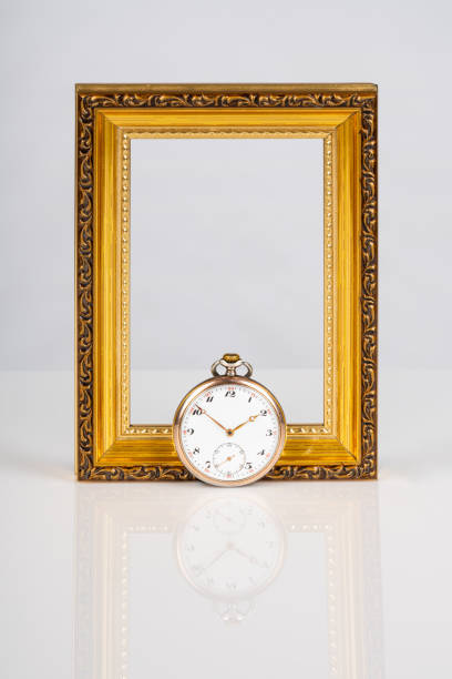 Old antique mechanical golden steel pocket watch in front of a empty wooden gold frame isolated on white background. stock photo