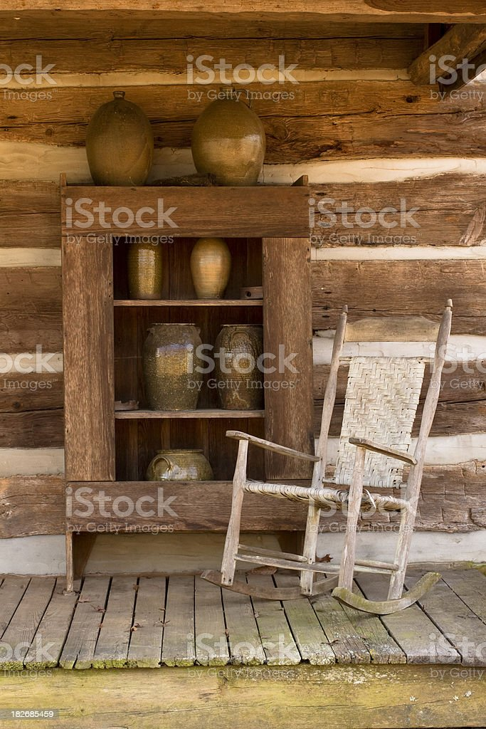 Old Antique Rocking  Chair On Wooden Deck Of Log Cabin royalty-free stock photo