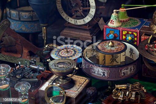 Barcelona, Spain - June 08 2018: Close-up on late 19th century, early 20th century antiques behind the window of a shop in Barcelona, Spain. The display is composed mostly of clocks, compasses, sextants, hourglasses and praxinoscopes.