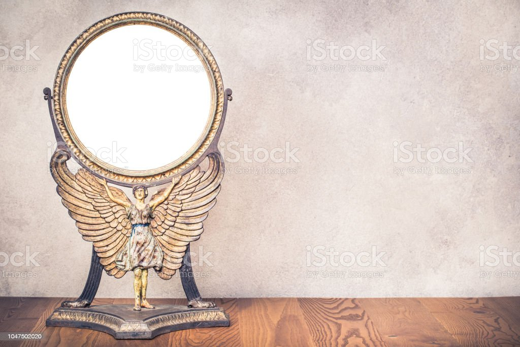 Old antique vintage cast iron desk makeup mirror frame blank holds on the stand in the form of goddess with wings or angel standing on table. Circa end of 1800s or early 1900s. Retro style filtered stock photo