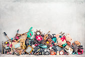 istock Old antiques and retro collectibles memorabilia dumped in a huge pile. Garage sale, attic room storage conceptual still life or disposal and recycling of outdated objects. Vintage style filtered photo 1262998444