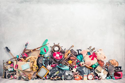 Old antiques and retro collectibles memorabilia dumped in a huge pile. Garage sale, attic room storage conceptual still life or disposal and recycling of outdated objects. Vintage style filtered photo