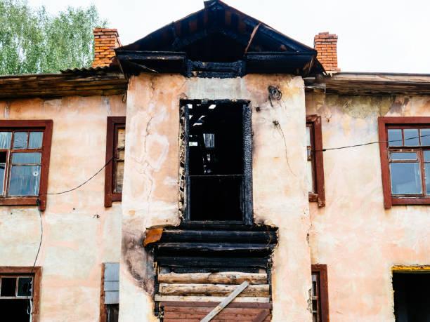gammalt lägenhetshus med svarta fönster efter branden. en dysfunktionell byggnad - brand sotiga fönster bildbanksfoton och bilder
