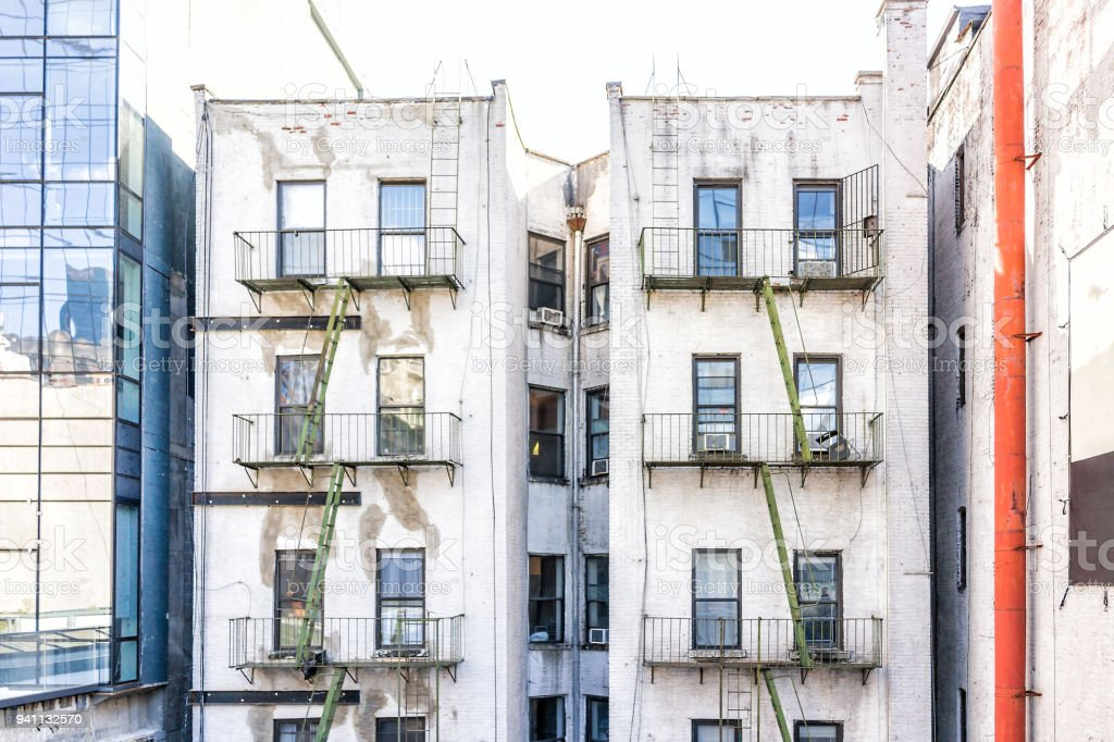 Old apartment condo building exterior architecture in Chelsea, NYC, Manhattan, New York City with fire escapes, windows, green ladders stock photo