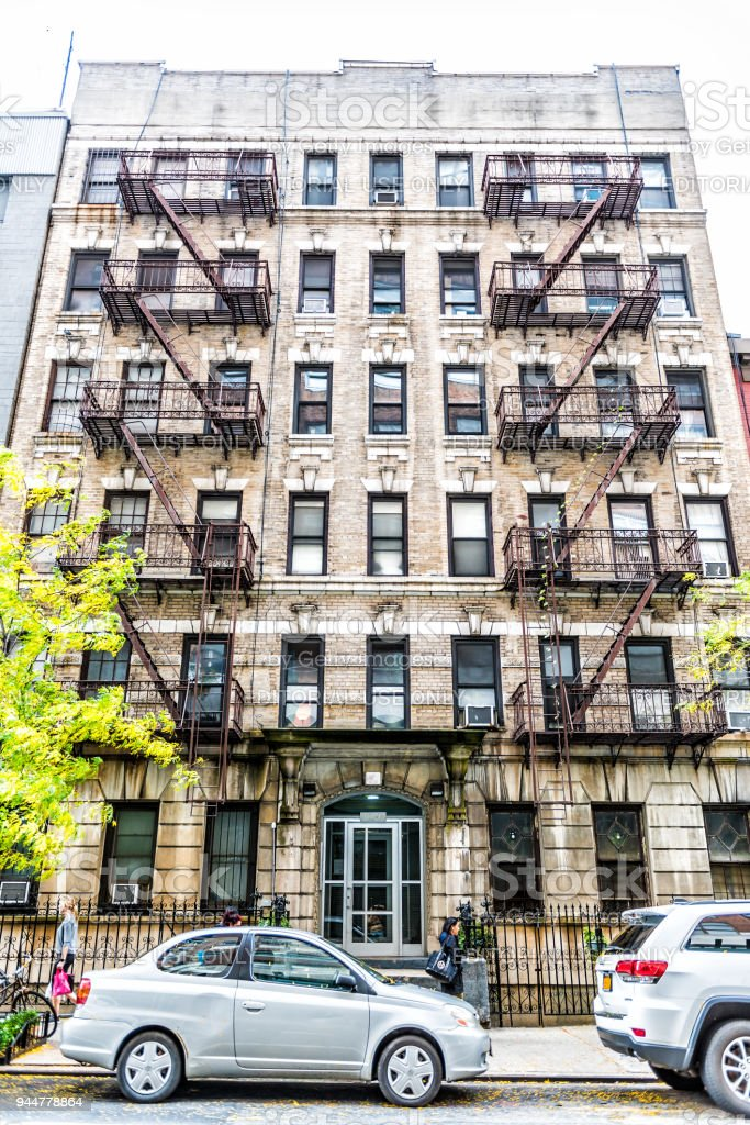 Old apartment condo building exterior architecture in Chelsea, NYC, Manhattan, New York City with fire escapes, windows, ladders stock photo