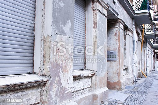 The image of old apartment exterior in downtown in east Berlin, Germany. The building exterior is damaged.