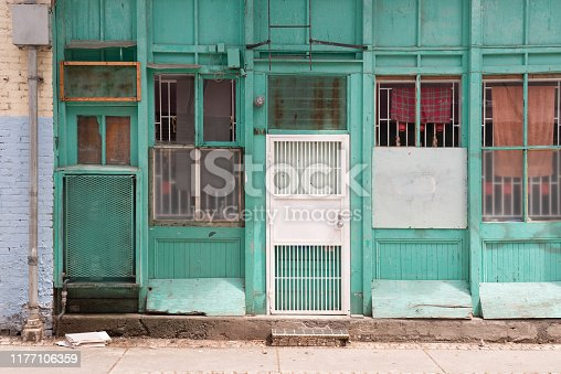 This is the front of the exterior of an aqua colored building with many mismatched doors and windows that are closed in Vancouver, Canada.