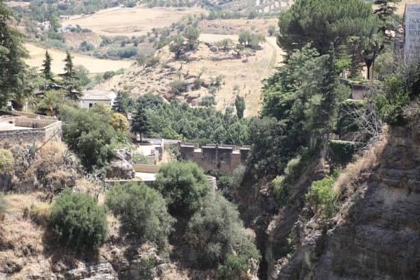 old arab moor bridge in ronda andalusia, spain - pejft stock photos and pictures