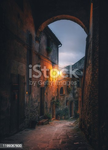 istock Old arched cobblestone street at night in medieval town Sorano, Tuscany, Italy 1199087600