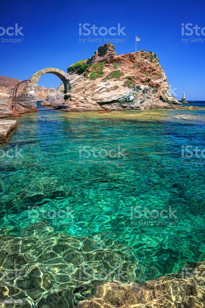 Old arched stone bridge and Lighthouse Tourlitis, in the beautiful town of Chora in Andros island, Cyclades, Greece stock photo