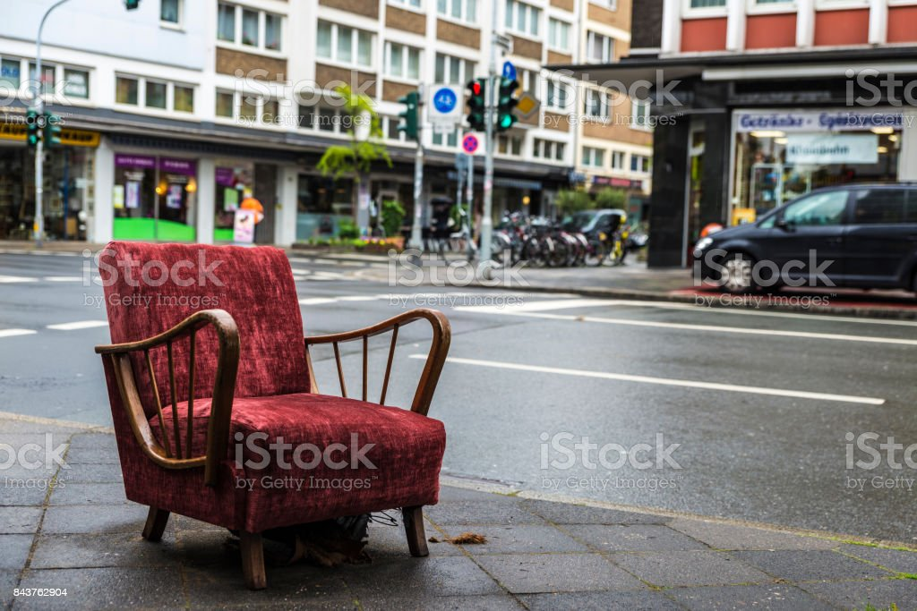 Old armchair vintage garnet lying on the street stock photo