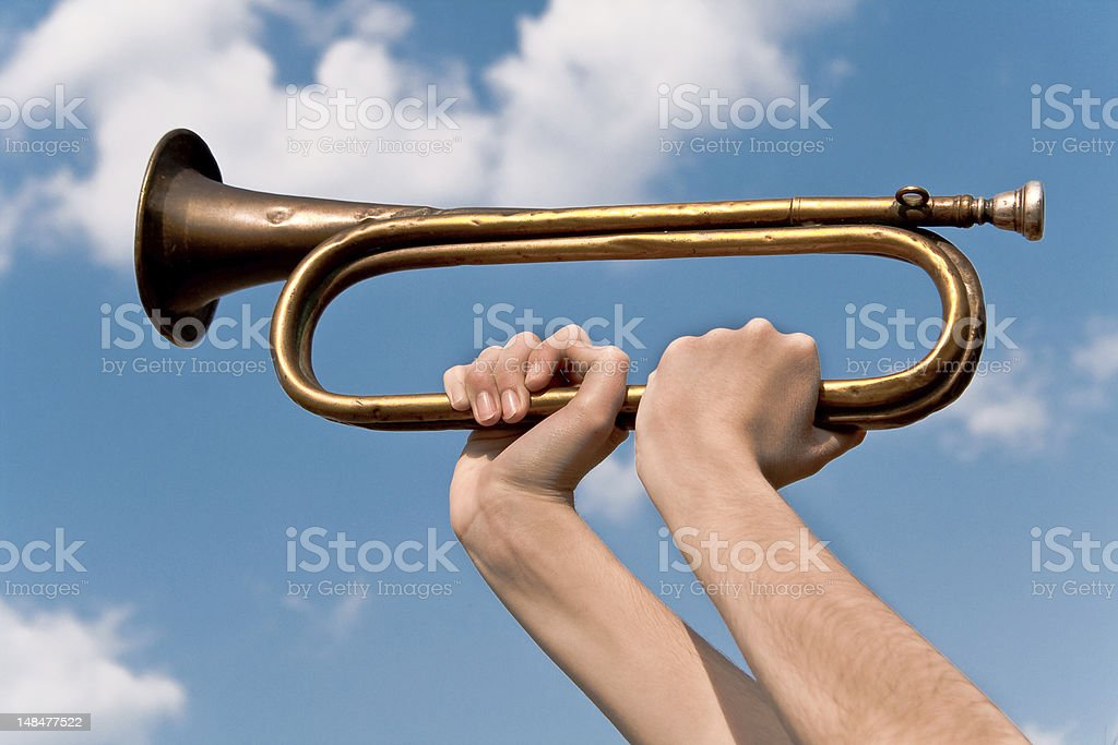 Old army trumpet in hand over blue sky royalty-free stock photo