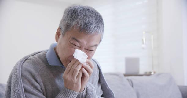 年老んだアジア人の男は風邪をひく - くしゃみ 日本人 ストックフォトと画像