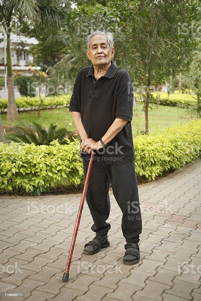 Old Asian man with walking stick royalty-free stock photo