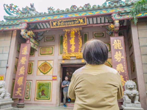 alte asiatische frauen stehen vor dem wat mangkon kamalawat - buddha figuren kaufen stock-fotos und bilder