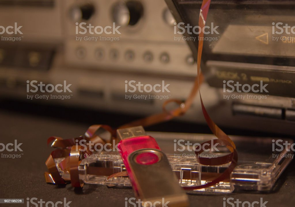 old audio cassettes with a tangled tape, cassette tape recorder and flash drive – zdjęcie
