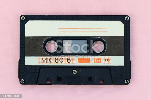 Old audio tape cassette on a pink background. Top view, old technology concept
