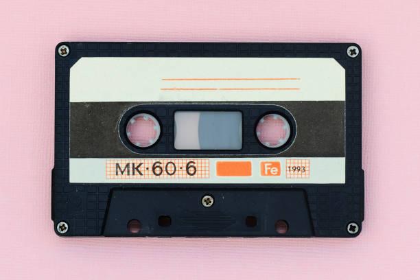 oude audio tape cassette op een roze achtergrond. top view, oude technologie concept - mengen stockfoto's en -beelden