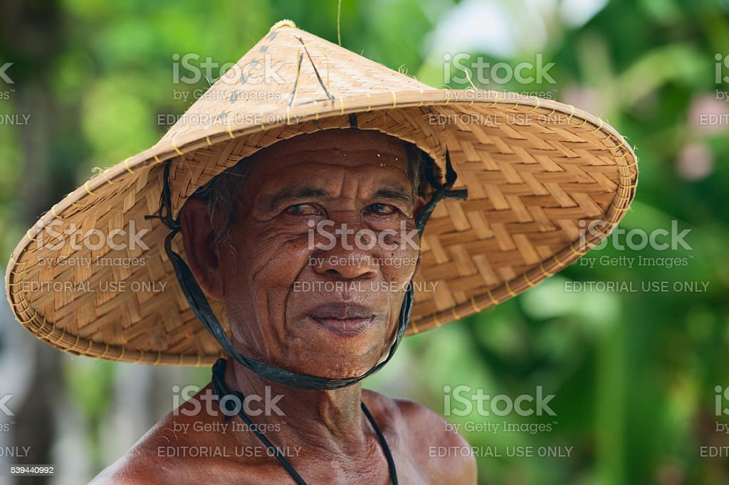 Old Balinese farmer with wrinkled face in traditional straw hat stock photo