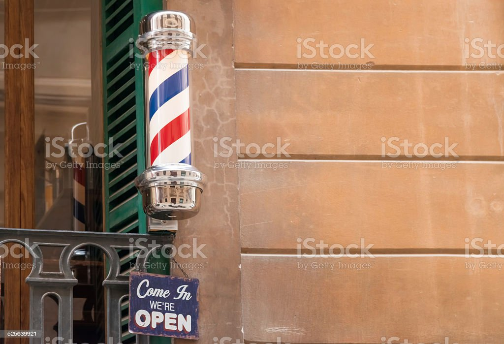 old barber pole on the wall stock photo