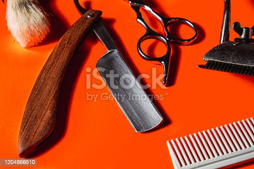 834518170 istock photo Old barber tools on an old beautiful Lush Lava surface. A razor, shaving brush, comb, hairdressers scissors, and a clipper 1204866510