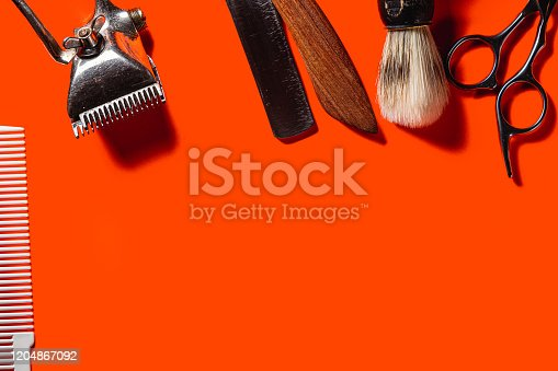834518170 istock photo Old barber tools on an old beautiful Lush Lava surface. A razor, shaving brush, comb, hairdressers scissors, and a clipper. horizontal orientation. copy space 1204867092