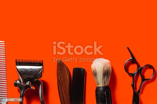 834518170 istock photo Old barber tools on an old beautiful Lush Lava surface. A razor, shaving brush, comb, hairdressers scissors, and a clipper. horizontal orientation. copy space 1204867105