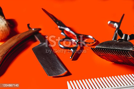 834518170 istock photo Old barber tools on an old beautiful Lush Lava surface. A razor, shaving brush, comb, hairdressers scissors, and a clipper 1204867140