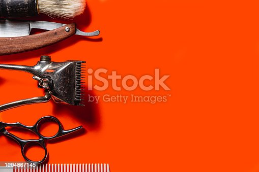 834518170 istock photo Old barber tools on an old beautiful Lush Lava surface. A razor, shaving brush, comb, hairdressers scissors, and a clipper. horizontal orientation. copy space 1204867145