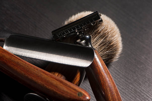 Old Barber Tools Old barber tools in wood. Brush, razor blade and razor on black textured wood. shaving brush shaving cream razor old fashioned stock pictures, royalty-free photos & images