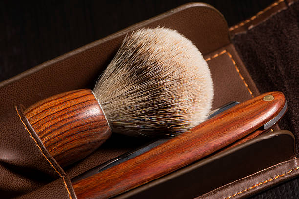 Old Barber Tools Old barber tools in wood. Brush and razor in leather case on black textured wood. shaving brush shaving cream razor old fashioned stock pictures, royalty-free photos & images
