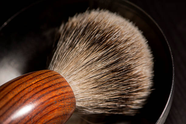 Old Barber Tools Old barber tools in wood. Brush in steel bowl on black textured wood. shaving brush shaving cream razor old fashioned stock pictures, royalty-free photos & images