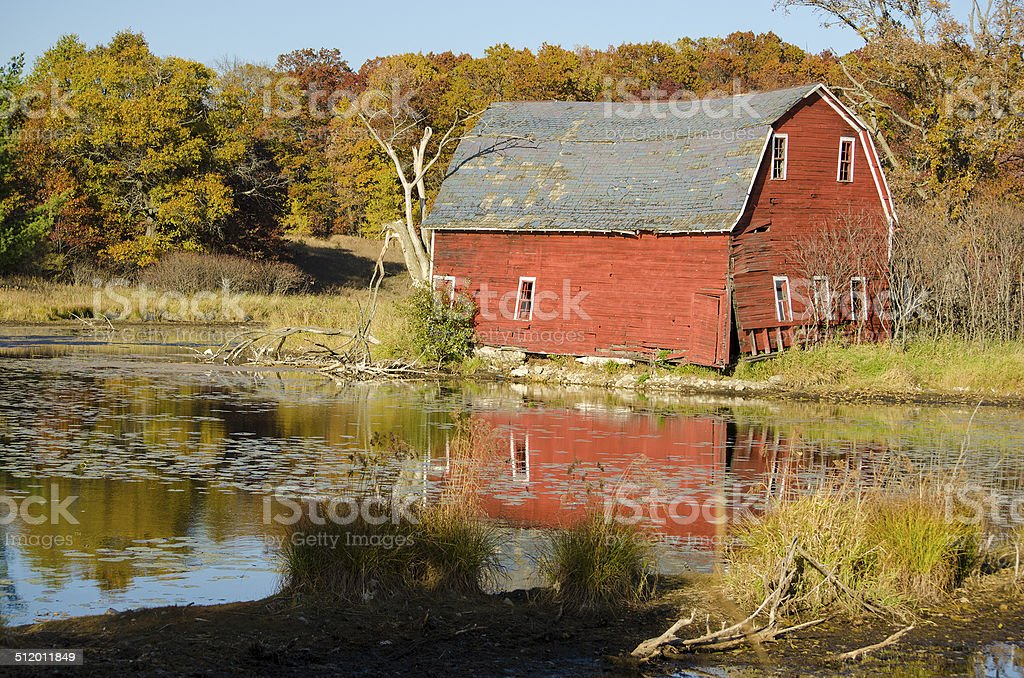Old barn by the pond stock photo
