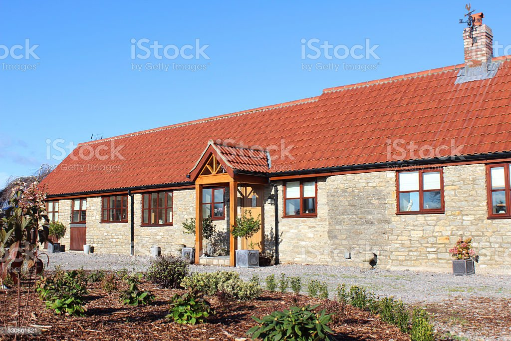 Old barn conversion house / bungalow, converted stables / outbuilding, front garden stock photo