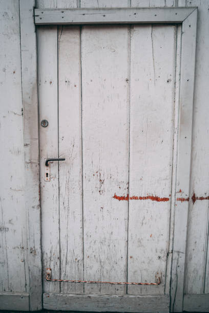 Old barn door (white) with signs of weathering stock photo