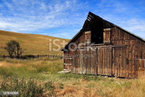 Beautiful wooden barn in rolling hills of golden grasses.